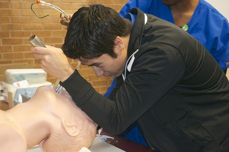 An intern from Pulaski Technical College works to place a breathing tube down the trachea of a manikin.