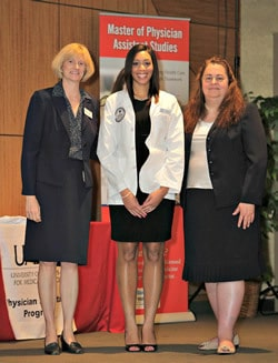 Physician assistant student Brittany Wilkerson poses for a photo after receiving her white coat from Nadja Button, M.H.S., (right) assistant professor in the PA program, and Patricia Kelly, Ph.D., chair of the Department of Physician Assistant Studies.